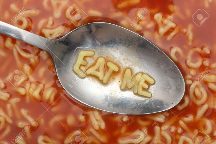 "Alphabet letters in spoon spell out ""Eat me"". Alphabet Soup Pasta. Close-up."